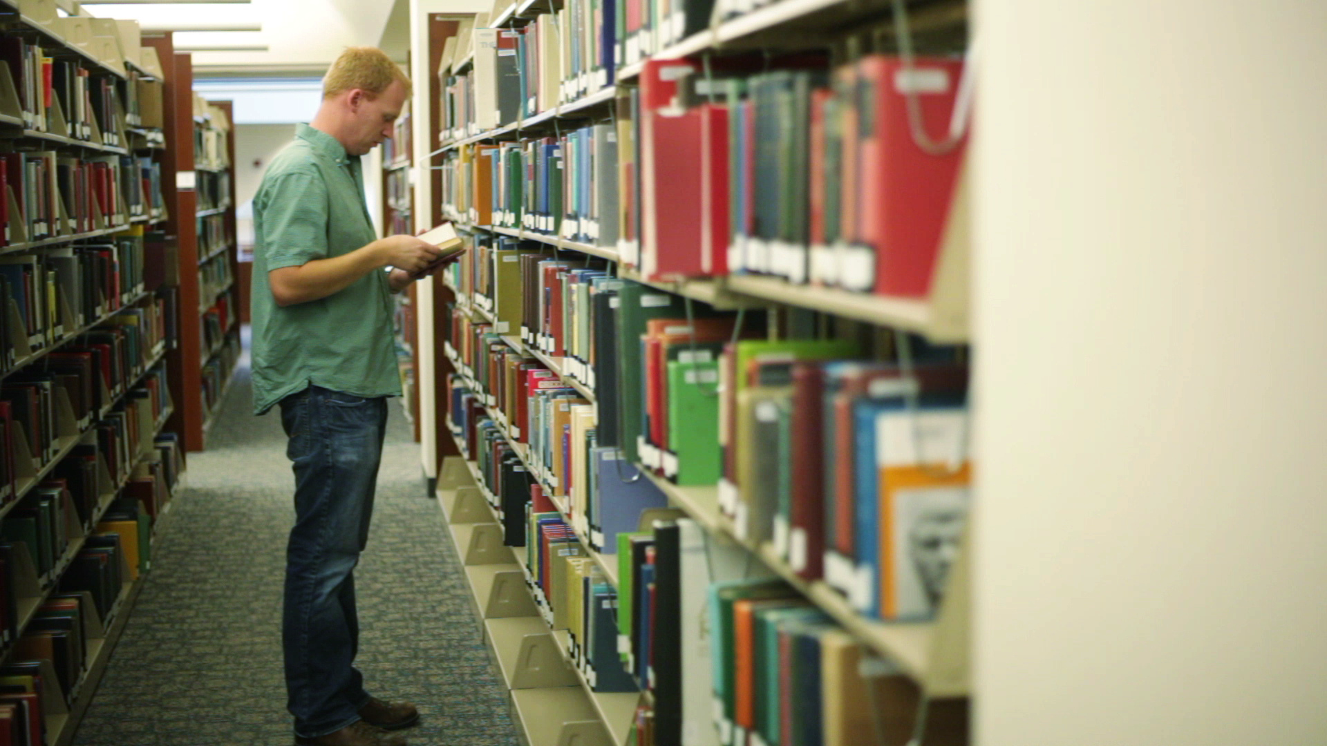 Student in library searching through a bookshelf