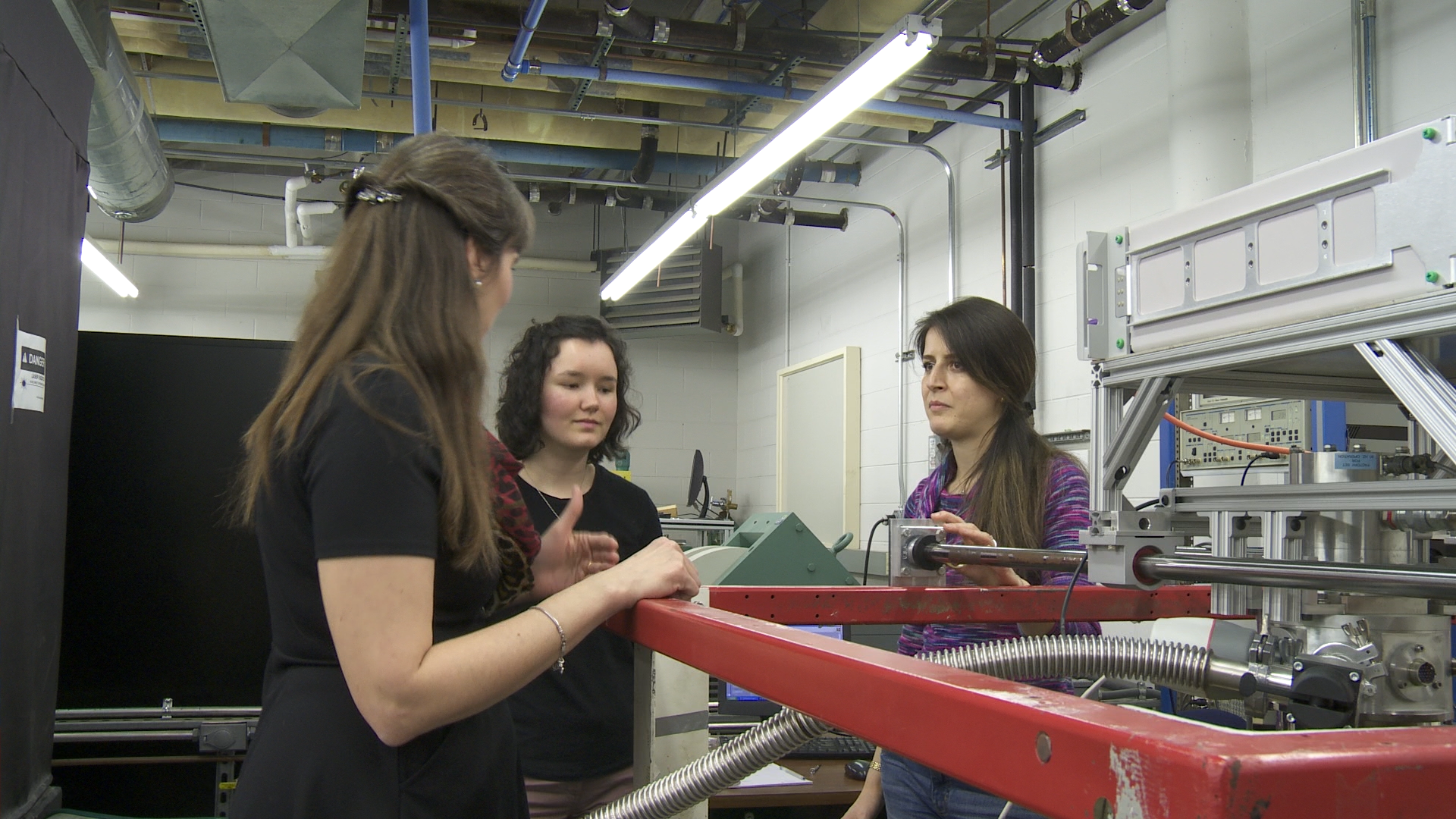 Students conferring around a machine