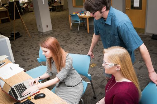 Students in computer lab getting help from teacher's aid